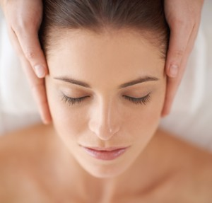 Close up shot of a young woman receiving a head massage at a spa